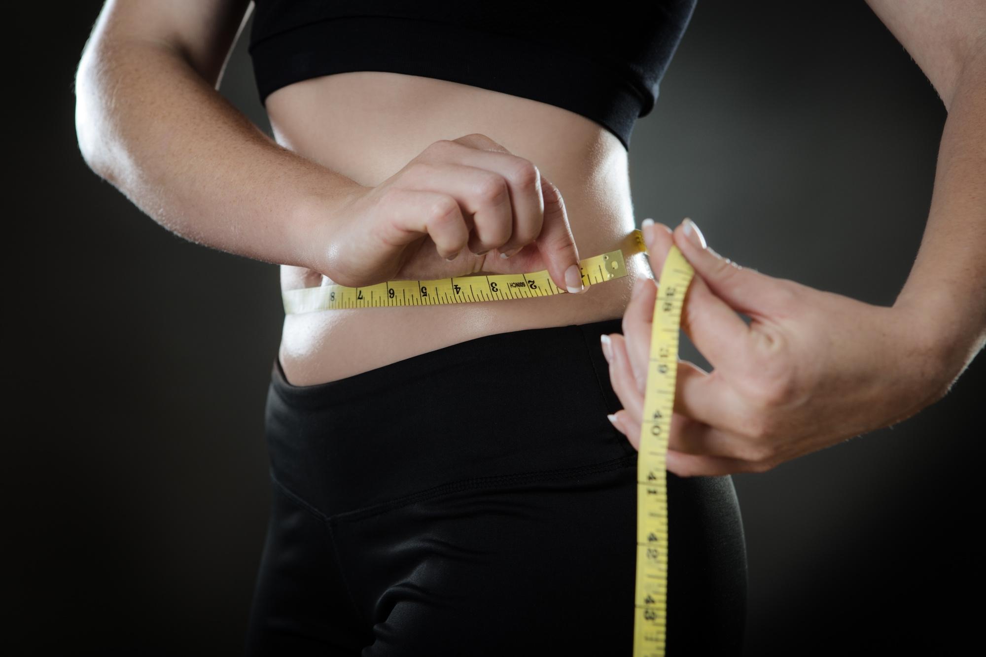 woman measuring her weightloss