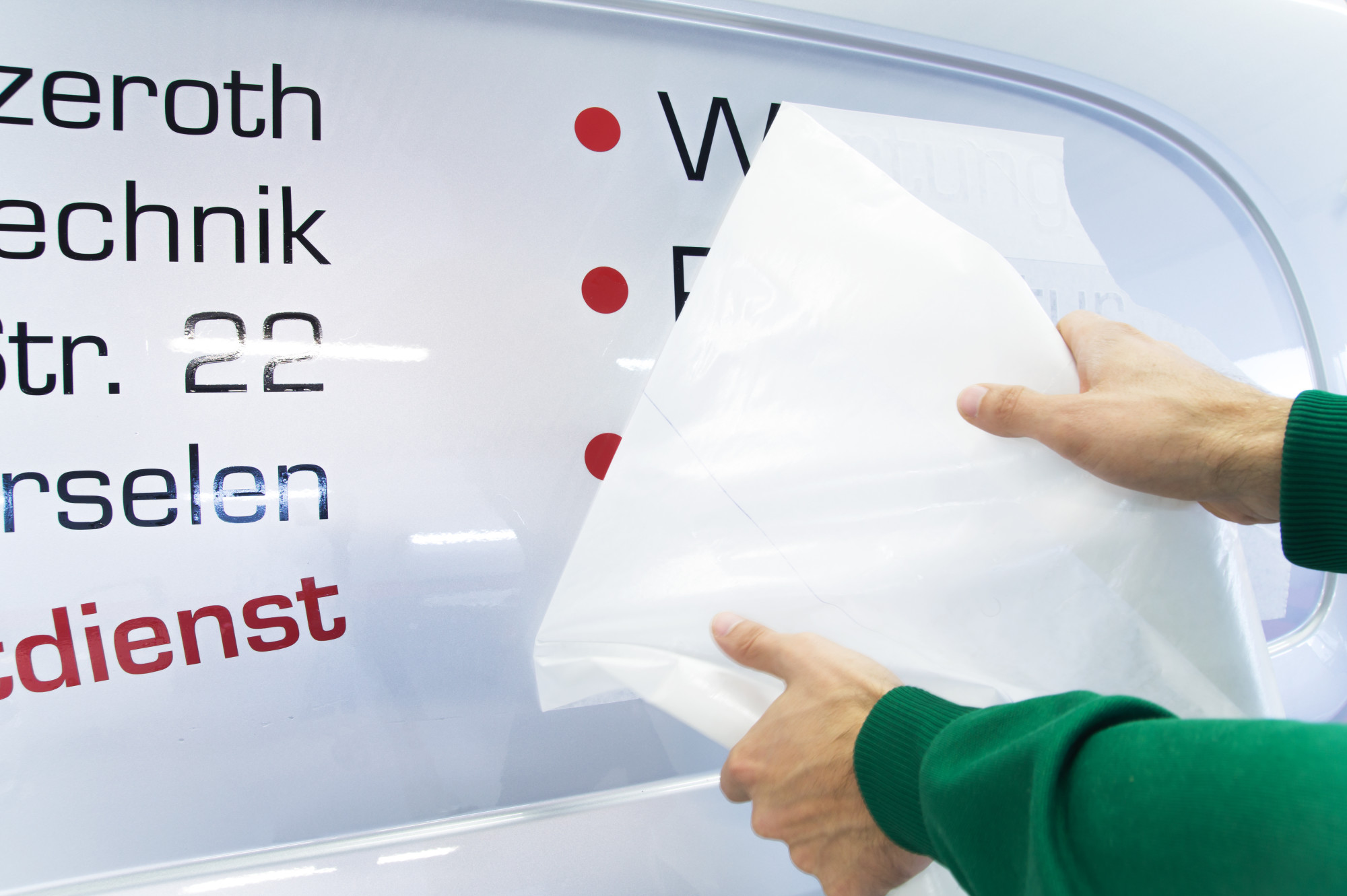 person applying auto decal